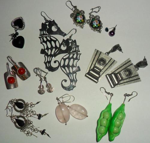 Czarne serduszka, te małe pojedyncze i koniki morskie - Glitter, a mniej więcej od lewej: srebrne z koralem, srebro i onyks - przywiezione z wakacji; skrzypce, różowy kwarc i modelinowe groszki - podarki; u góry jest porcelana emaliowana i oprawiona srebrem -po prababci; duże, ciężkie trapezy mam z C&A lub H&M.